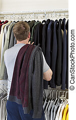 Mature man making decision of which sweater to wear