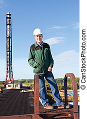 Mature man manual worker in white hardhat in roof against industrial chimney