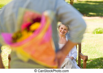Mature man offering flowers to his wife