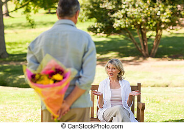 Mature man offering flowers to his