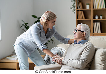 Mature man on couch holding hand of daughter while looking at her during chat