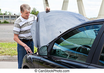 Mature man opens car hood to repair breakdown in his car
