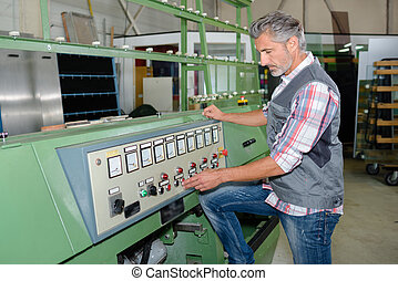 Mature man operating industrial machine