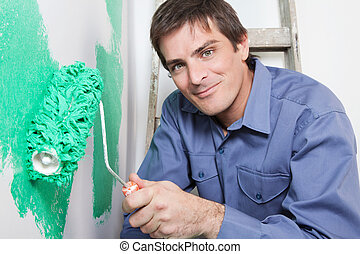 Mature man painting the wall with a roller