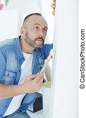 mature man painting wall in the home