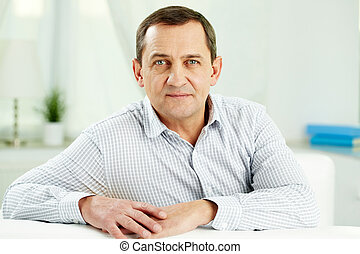 Mature man - Portrait of mature man looking at camera while...