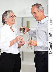 mature man pouring sparkling wine to his wife