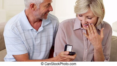 Mature man proposing to his partner on the couch at home in...