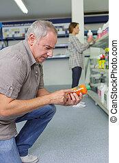 mature man purshasing item in hardware store