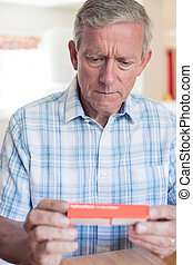 Mature Man Reading Information On Drug Packaging