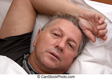Mature man resting in bed