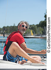 mature man sailing alone