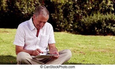 Mature man sat on the grass using h