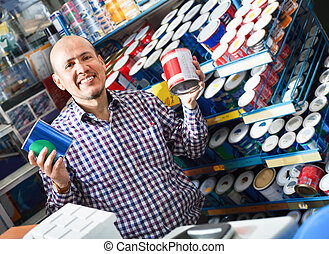 Mature man selecting wall paint and emulsion in store - ...