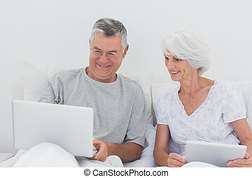 Mature man showing something on his laptop