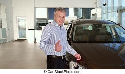 Mature man shows thumb up near the car at the dealership