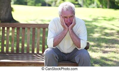 Mature man sitting alone on a bench