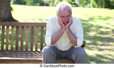 Mature man sitting alone on a bench