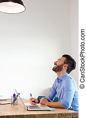 Mature man sitting at office and smiling