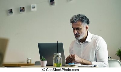 Mature man sitting at the table in a cafe, using laptop. -...
