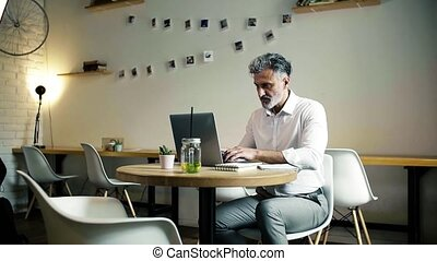 Mature man sitting at the table in a cafe, using laptop....