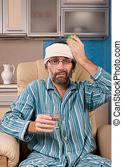 mature man sitting in chair with glass of water