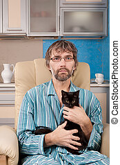man sitting in chair with kitten