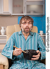 man sitting in chair with pot
