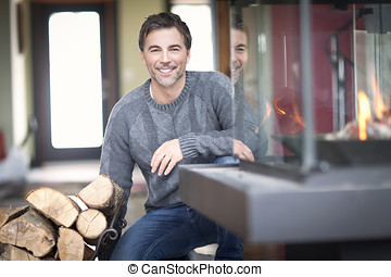 Mature man smiling at the country house. At the Fireplace