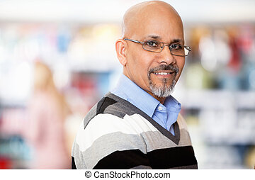 Mature man smiling while shopping