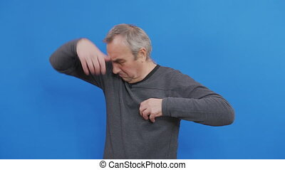 Mature man sniffing his armpit, something stinks very bad. Bad smells concept