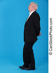 mature man standing in profile against blue background