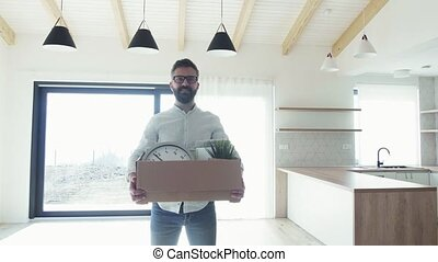 Mature man standing in unfurnished house, holding a movinbg...