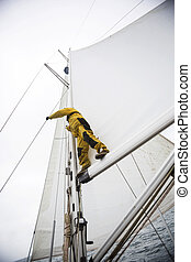 Mature Man Standing On Yacht Boom Against Sky