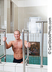 Mature man stepping out of the pool