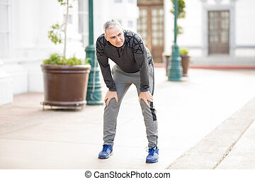 Mature man stopping for a breather after long run