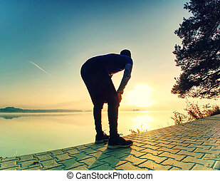 Mature man  stretches muscles while resting after jogging.