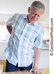 Mature Man Suffering From Backache Whilst Getting Out Of Chair At Home