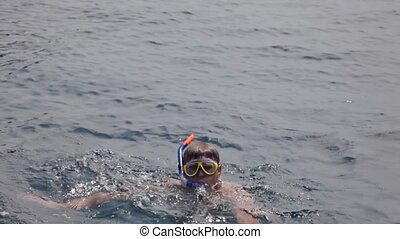 mature man swims at the ocean with a mask for a snorkeling