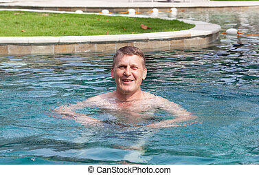 mature man swims in the pool hotel