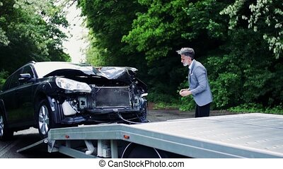 Mature man taking pictures of a broken car after an accident.