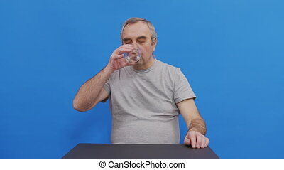 Mature man taking pill drinking water having health problem. Pensive grandfather suffering from alzheimer or parkinson with painful face expression. Isolated on blue