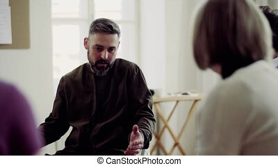 Mature man talking to other people during group therapy. - A...