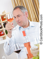 mature man tasting glass of rose wine at home