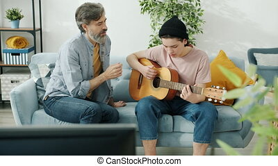 Mature man is teaching teenage son to play the guitar while sitting on sofa in light apartment. Happy choildhood and musical instruments concept.