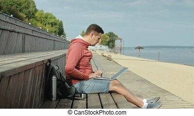 Mature man, tourist using a laptop, sitting on the beach on a wooden bench