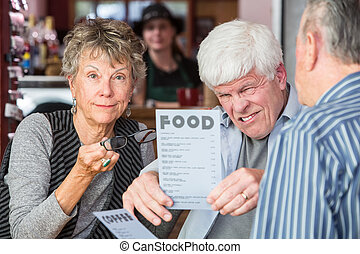 Mature Man Trying to Read Menu Without Glasses - Man has...