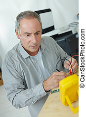 mature man using multimeter