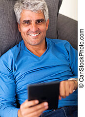mature man using tablet computer