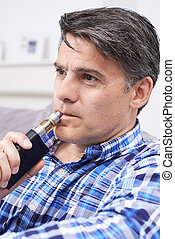 Mature Man Using Vapourizer As Smoking Alternative